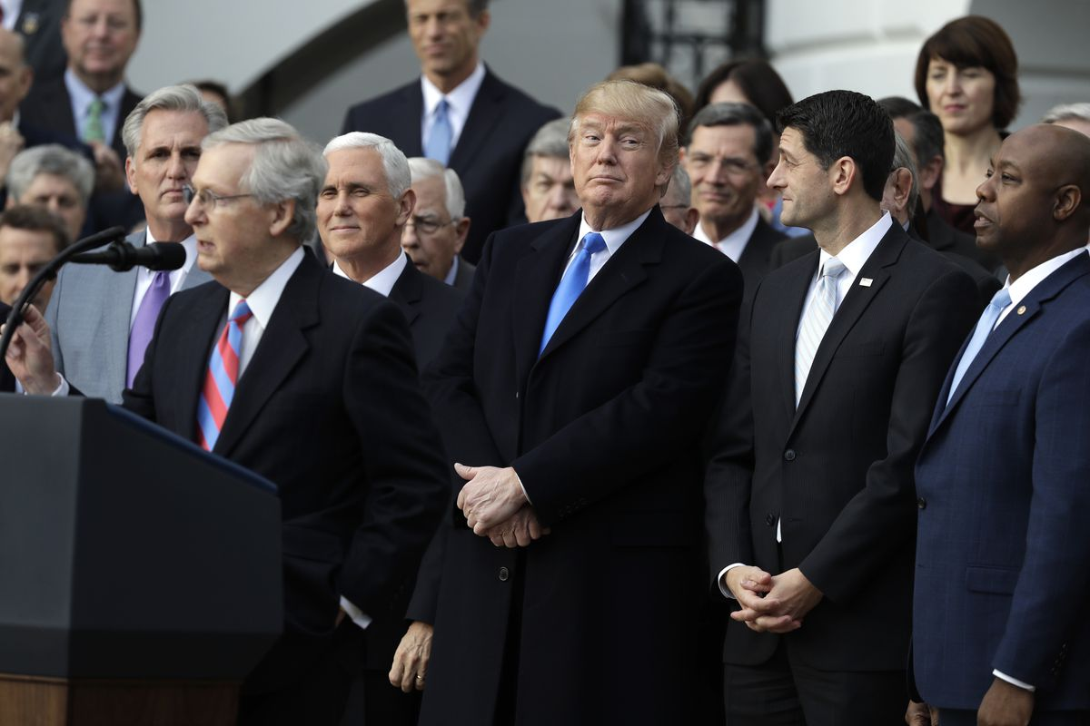 Senate Majority leader Mitch McConnell of Ky., speaks as President Donald Trump, House Speaker Paul Ryan of Wis., and Sen. Tim Scott, R-S.C., right, listen during a bill passage event on the South Lawn of the White House in Washington, Wednesday, Dec. 20,