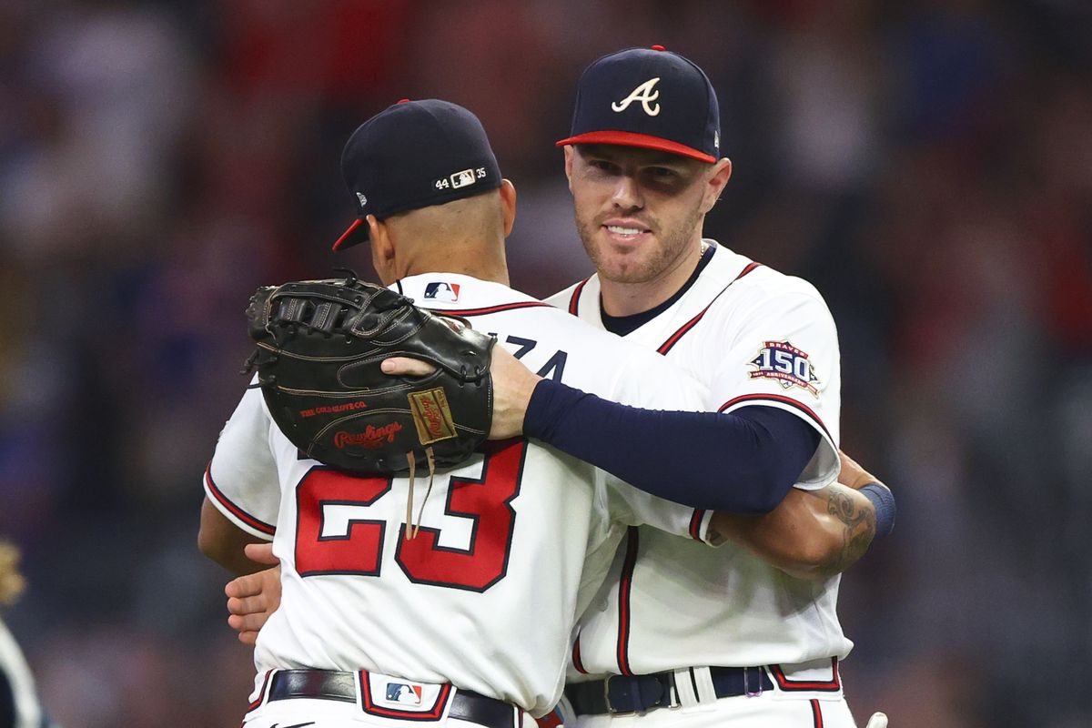 Freddie Freeman #5 reacts with Ehire Adrianza #23 of the Atlanta Braves at the conclusion of their 6-5 victory over the New York Mets at Truist Park on October 2, 2021 in Atlanta, Georgia.
