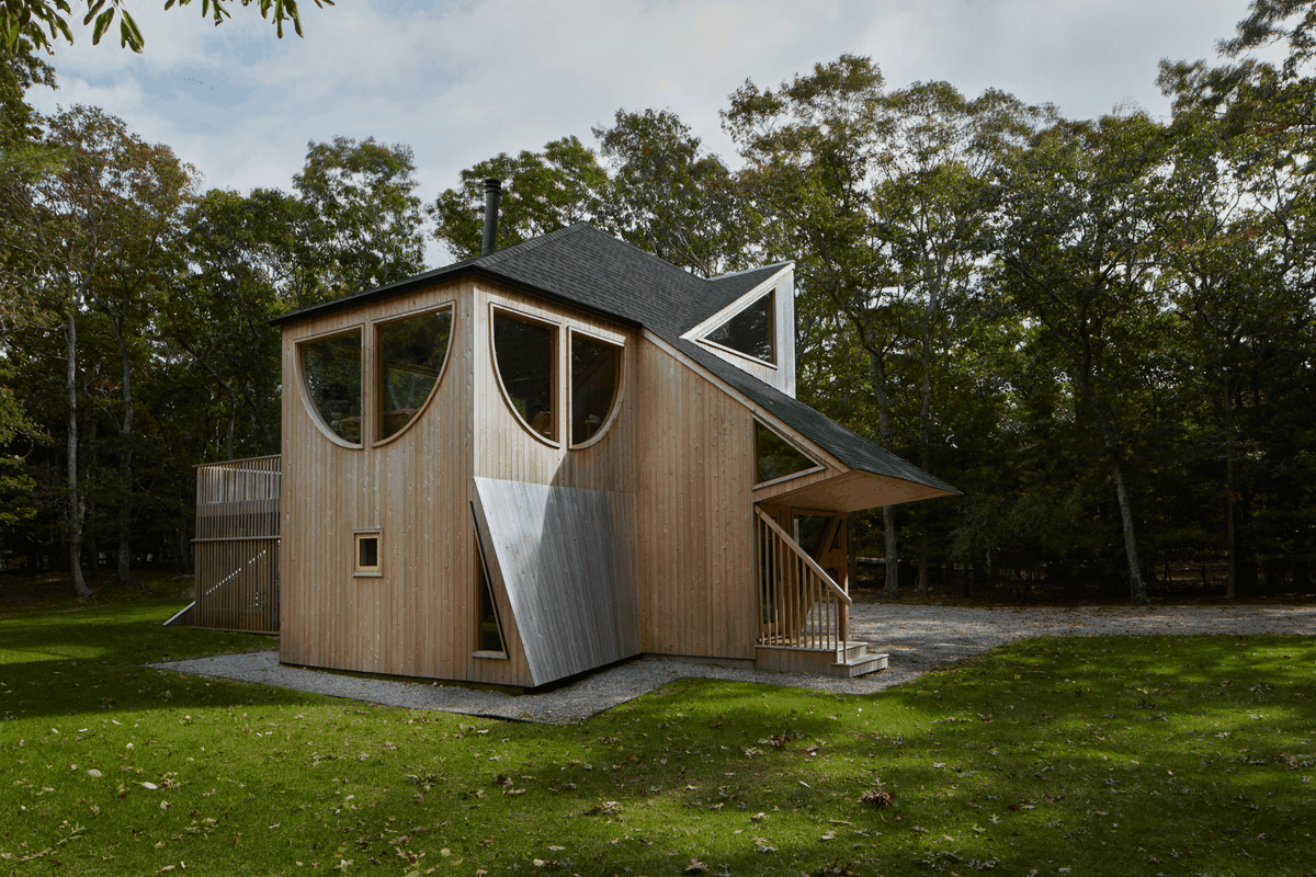 Exterior of home with irregular shape and large windows surrounded by woods.
