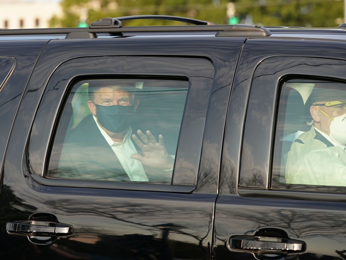President Donald Trump waving in the back of a motorcade outside of Walter Reed Medical Center.