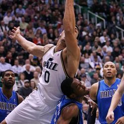 Enes Kanter of the Utah Jazz is undercut on a rebound by Rodrigue Beaubois of the Dallas Mavericks during NBA basketball in Salt Lake City, Monday, Jan. 7, 2013.