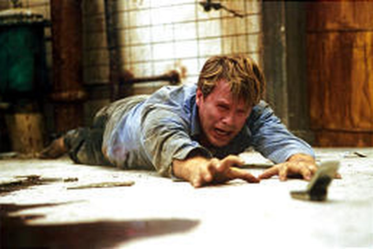 """Dr. Lawrence Gordon, played by Cary Elwes, reaches for a cell phone after finding himself chained to a pipe in a decrepit chamber in """"Saw."""""""