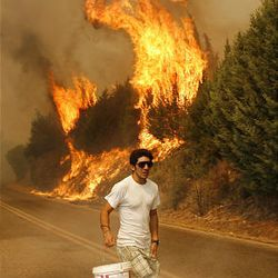 A man carrying a bucket runs to help contain a fire outside Marathon, northeast of Athens, Saturday, Aug. 22, 2009. A wilfire was raging unchecked, fanned by high winds, burning a pine forest, brushes and olive groves. Three vilages near Marathon were cut off, firefighters said. (AP Photos/Dimitri Messinis)
