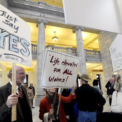 The Revs. Scott Dalgarno and Catherine Putnam-Netto with Wasatch Presbyterian Church hold signs during the Utahns for the Medicaid Expansion rally in the rotunda at the state Capitol on Wednesday, Nov. 20, 2013, in Salt Lake City. The group rallied to show Gov. Gary Herbert he has support if he decides to expand Medicaid.
