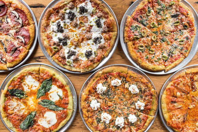 A variety of pizzas spread out on a table.