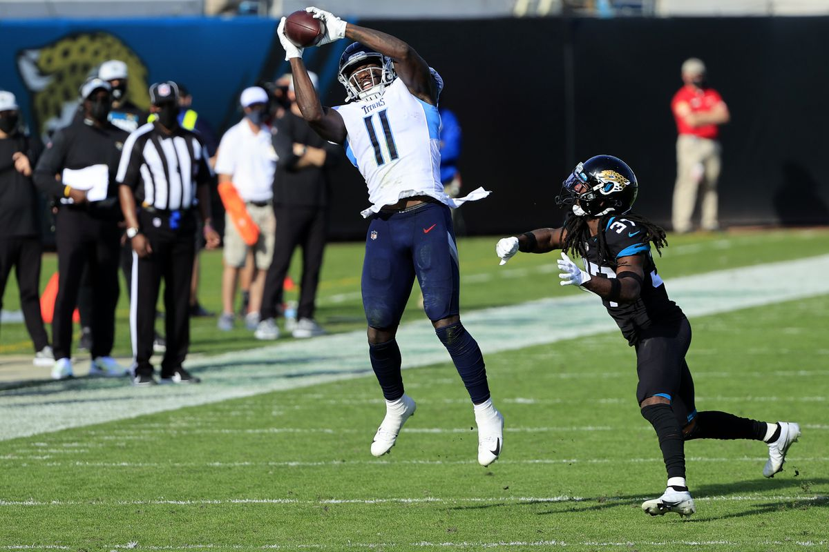 A.J. Brown #11 of the Tennessee Titans makes a catch over Tre Herndon #37 of the Jacksonville Jaguars at TIAA Bank Field on December 13, 2020 in Jacksonville, Florida.