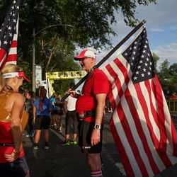 Kandi Rasmussen and Andrew Pullens carry American flags after finishing the Deseret News 10K at Liberty Park in Salt Lake City on Friday, July 23, 2021.