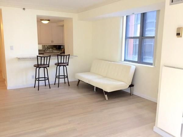 A living room empty other than a couch and two stools in front of a kitchen counter.