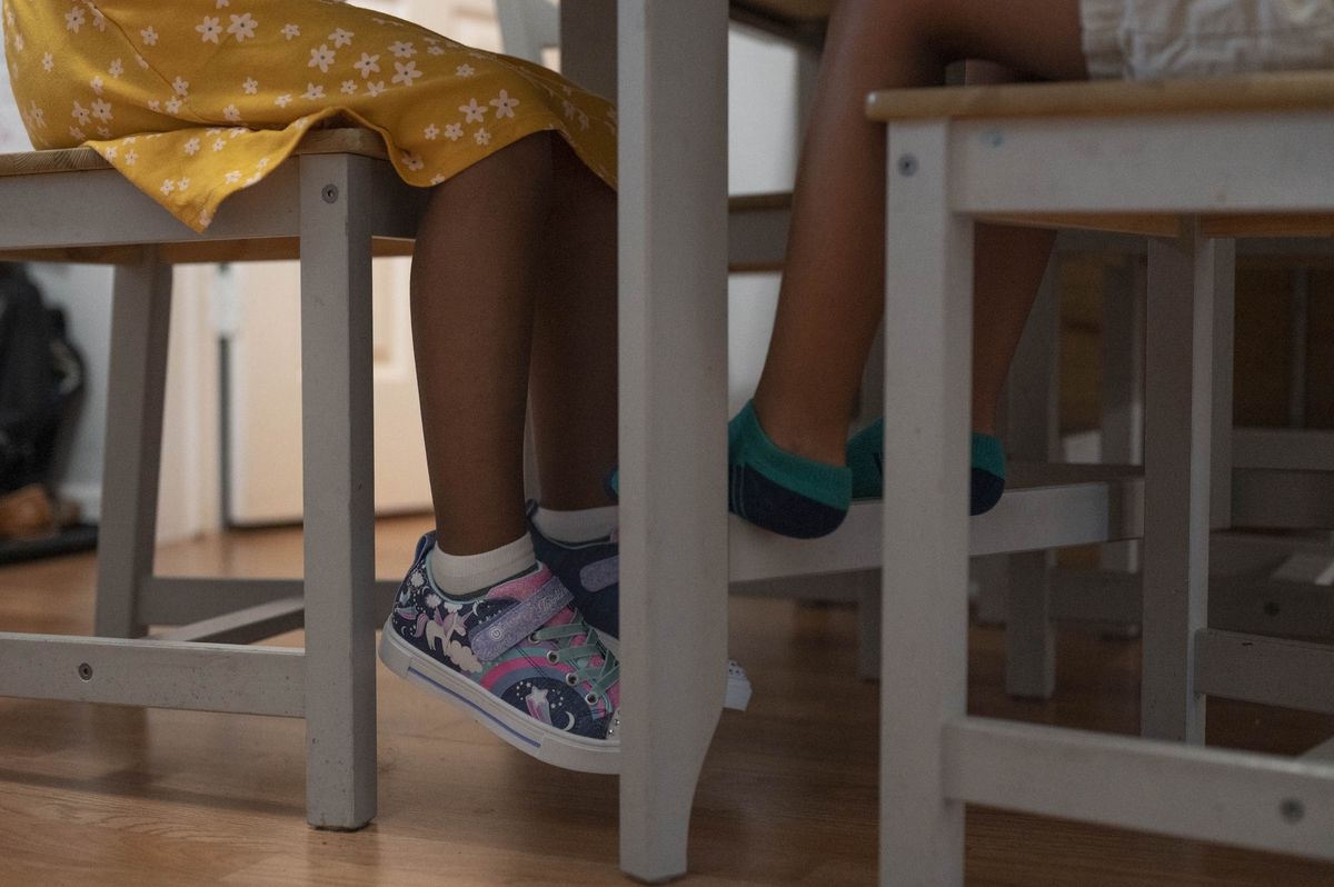 The legs of a sister and brother hang off of chairs as they sit in the dining room. The little girl is wearing a pair of unicorn sneakers.