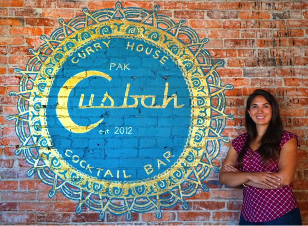 Soophia Hussain poses with a mural at Cusbah