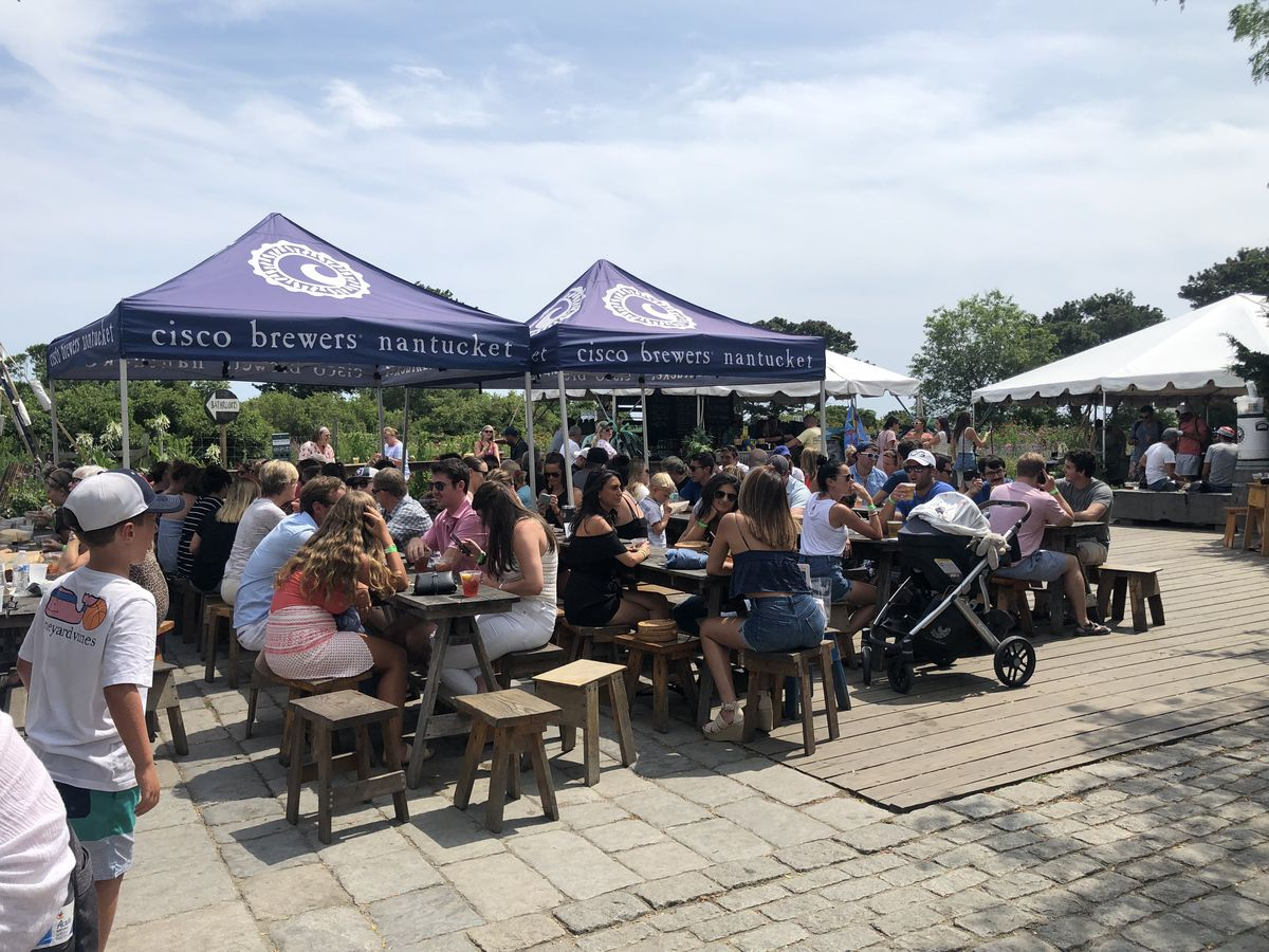 Many people sit on wooden stools at picnic-style tables, some in the sun and some under Cisco-branded blue tents, drinking beer