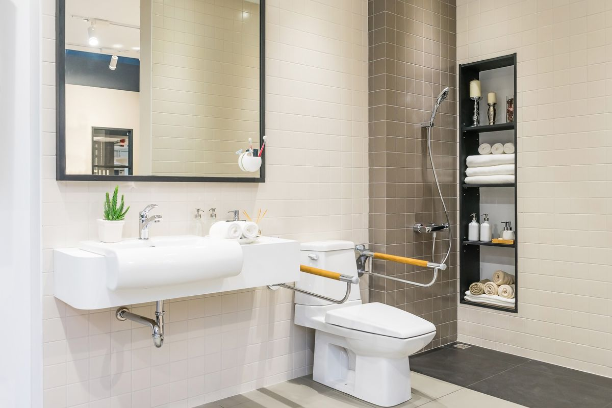 A bathroom modified for senior accessibility with stabilizers on either side of the toilet, a no-step-up shower, and large sink.