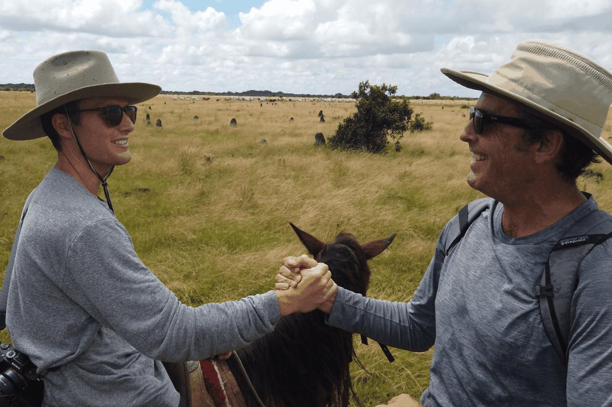 Bob Woodruff and Mack Woodruff shake hands while on horses in Rogue Trip on Disney Plus