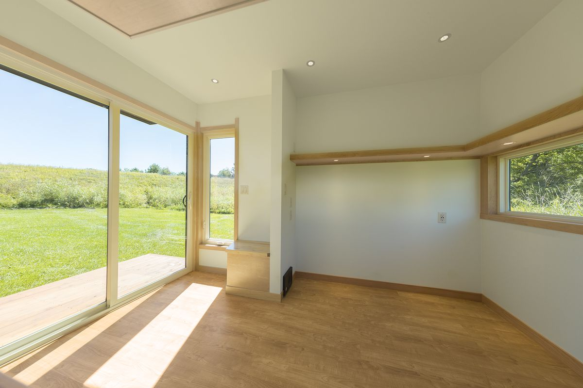 Interior of a small dwelling with glass walls, light wood floors, and white walls. A long rectangular window is in the rear wall.