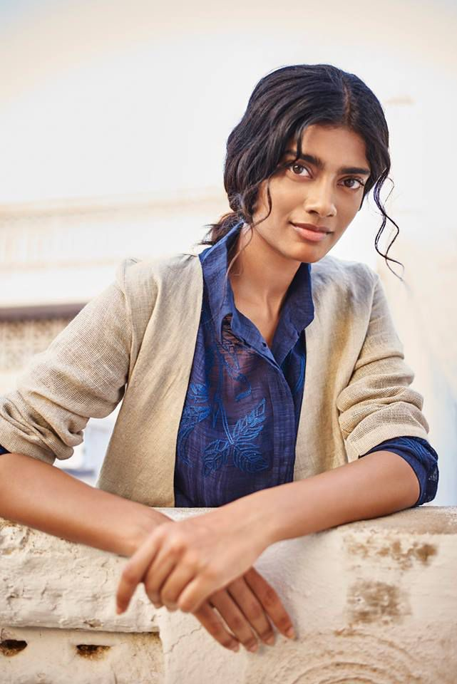 A model in a blue embroidered shirt and cream jacket