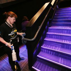 Nicki Forbes cleans handrails after cleaning the seats and food trays between movies at the Megaplex Theatres at Jordan Commons in Sandy on Friday, March 13, 2020.