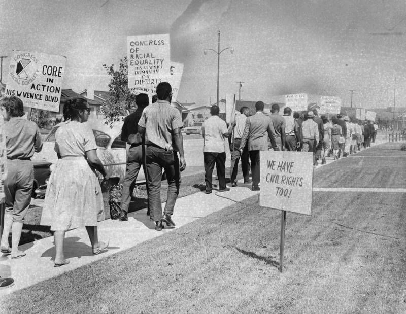 """A grainy archival photo of dozens of men and women walking down a sidewalk and carrying protest signs reading """"CORE in Action"""" in a residential neighborhood. A counter-protest sign staked in one lawn reads """"We have civil rights too!"""""""