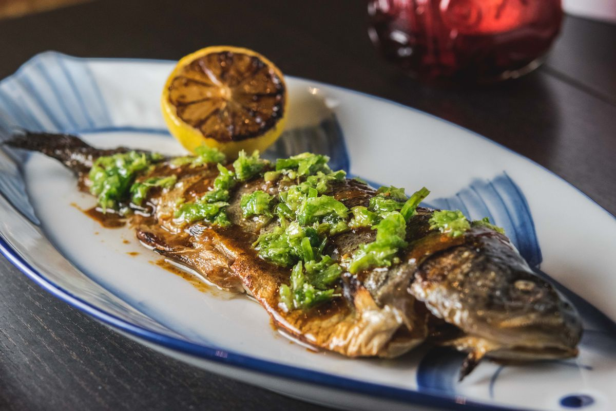 A whole trout sits on a plate, topped with a green sauce and accompanied by a half a grilled lemon