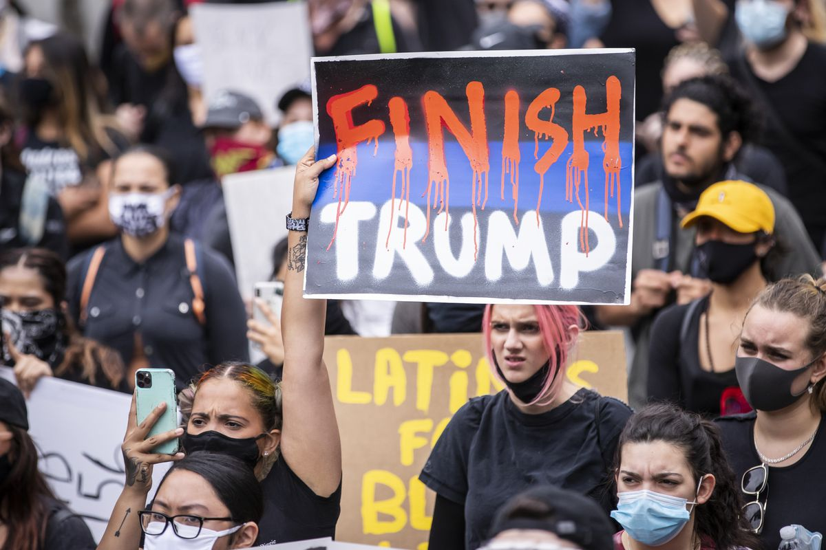 """A protester holds a sign that says, """"FINISH TRUMP"""" with the Finish in red dripping letters among the large crowd in Foley Square in Manhattan."""