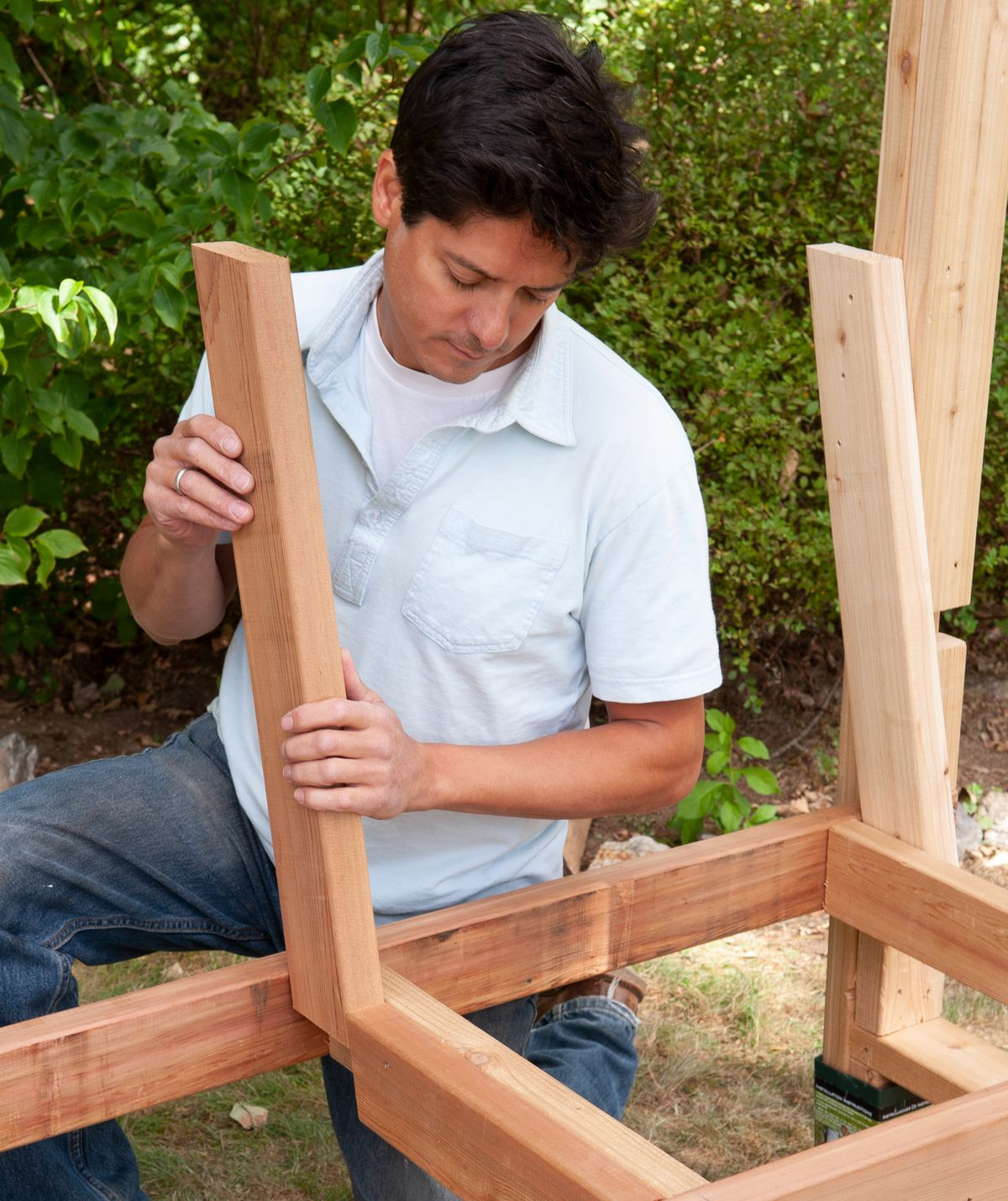 Man Secures Center Support Of Arbor Bench