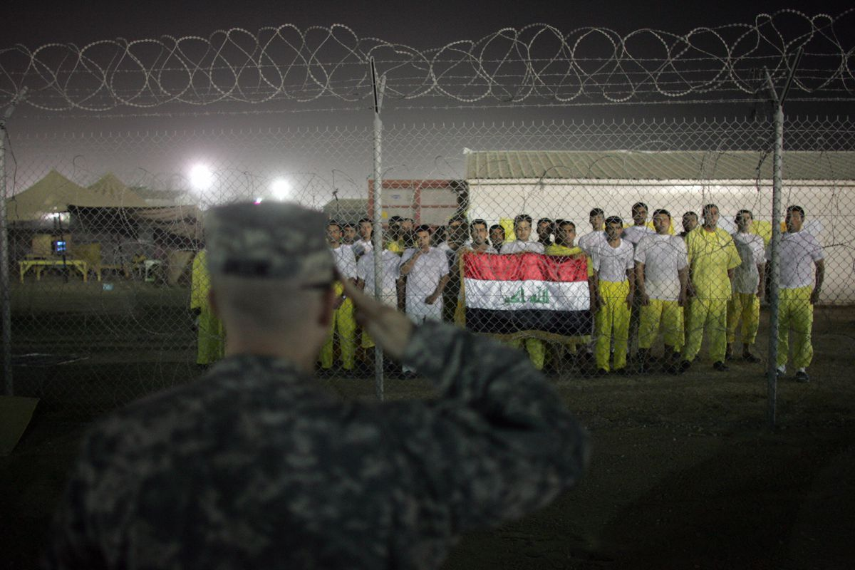 A US soldier salutes Iraqi detainees singing the national anthem at Camp Bucca in 2008.