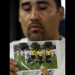 In this Thursday, May 2, 2013 file photo, Jose Lopez points to an undated photo of Ricardo Portillo, center, his brother-in-law, following a news conference, at Intermountain Medical Center, in Murray, Utah. Portillo, a 46-year-old soccer referee who was punched by a teenage player during a game and later slipped into a coma died Saturday night, May 4, 2013, police said.
