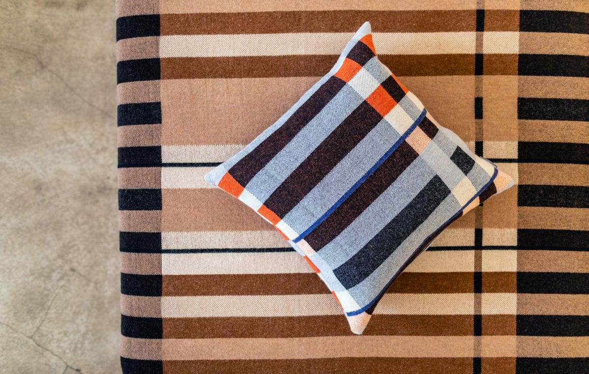 A striped blanket. On top of the striped blanket is a striped pillow.