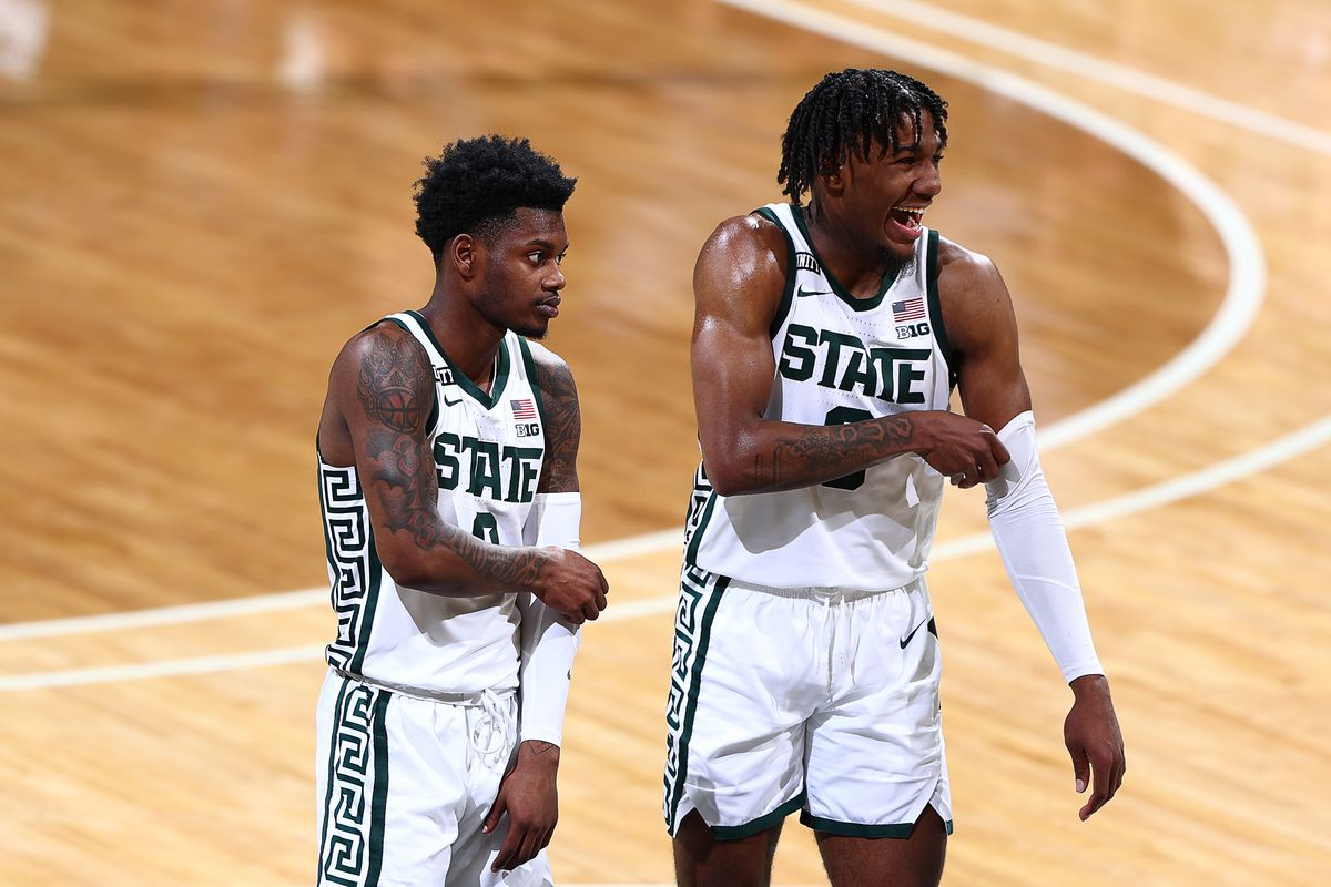 Rocket Watts and Aaron Henry of the Michigan State Spartans walk onto the court after a time out in the first half of the game against the Ohio State Buckeyes at Breslin Center on February 25, 2021 in East Lansing, Michigan.