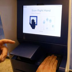 Ricky Gambill, CLEAR Salt Lake City supervisor, demonstrates how to scan fingerprints for the company's a new biometric, fee-based service that allows travelers to move past manual ID verification lines using fingerprints and iris scans, at the Salt Lake City International Airport in Salt Lake City on Wednesday, July 12, 2017.