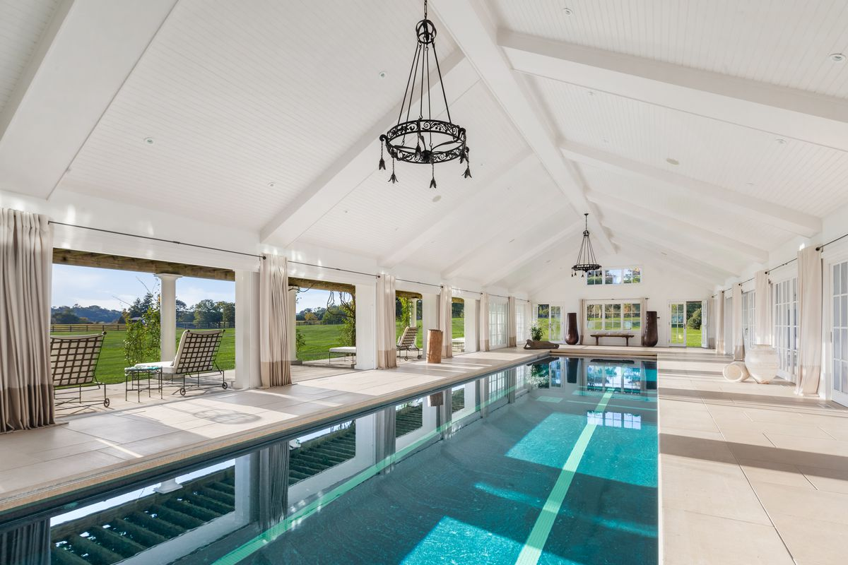 An indoor lap pool sits inside a peaked white building flanked by French doors overlooking the grounds.