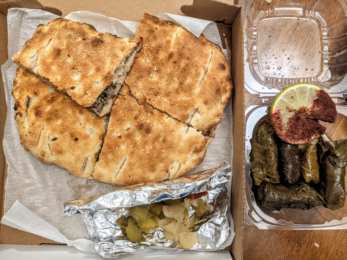 Overhead view of takeout Egyptian food —a pita stuffed with ground meat sits in a pizza box, and there's a container of grape leaves.