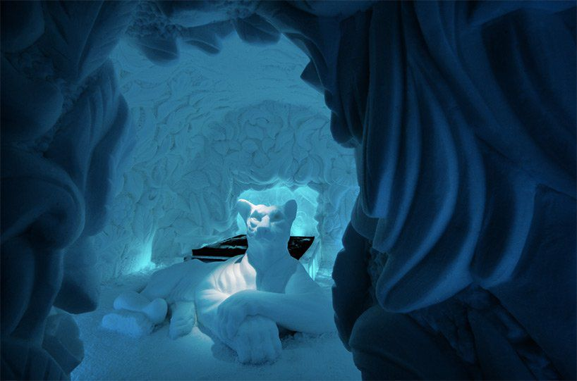 An ice cave with a giant cat sculpture.
