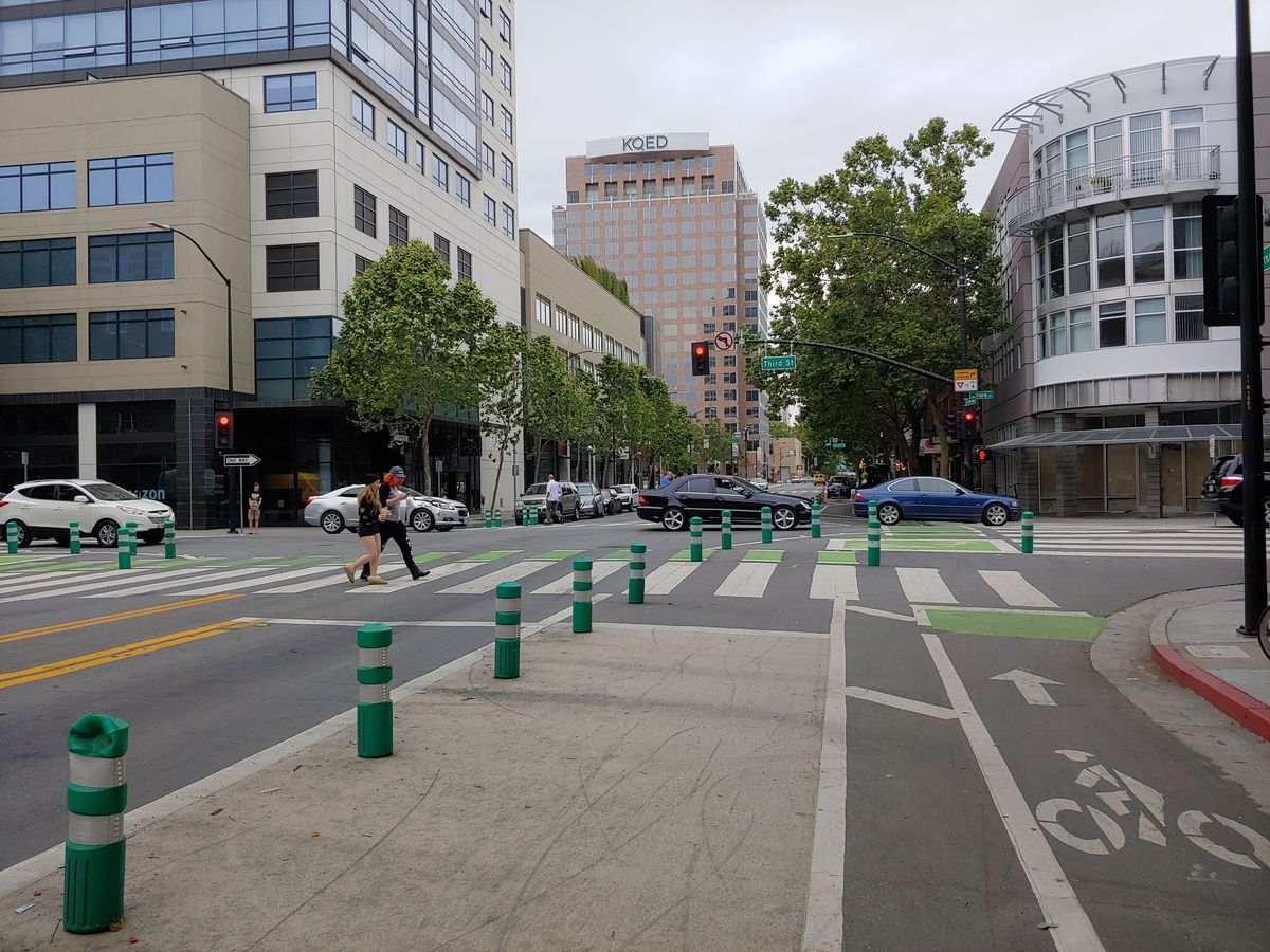 A busy downtown crosswalk is seen with wide bike lanes and walking paths delineated by bright green bollards.