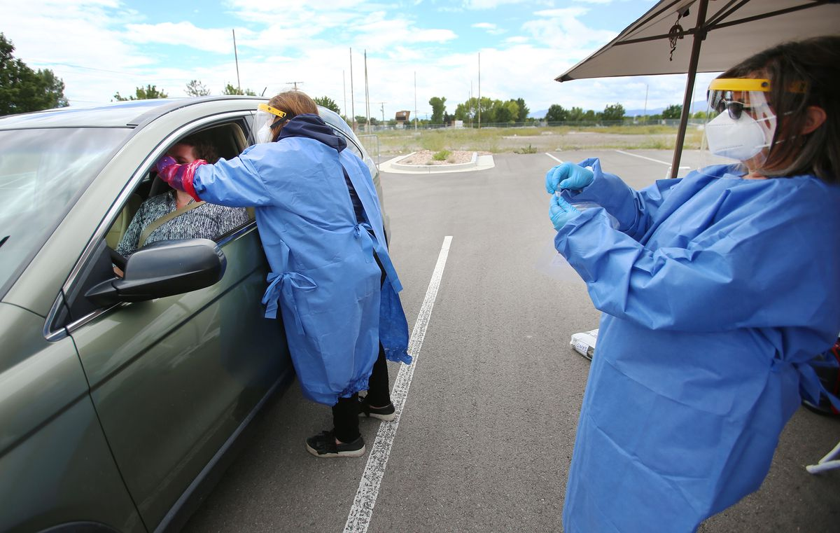 Eve Kovacs, of TestUtah, administers a COVID-19 test to Emily Johnson as Mary Hickman stands at the right at a testing site near the Utah Olympic Oval in Kearns on Tuesday, June 30, 2020.