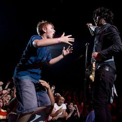 A young fan, left, jumps on the stage with Billie Joe Armstrong at the EnergySolutions Arena in Salt Lake City on Sunday.
