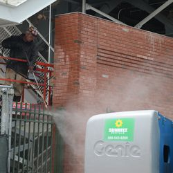 2:03 p.m. Power washing the wall and fence, in the right-field corner, on Sheffield -