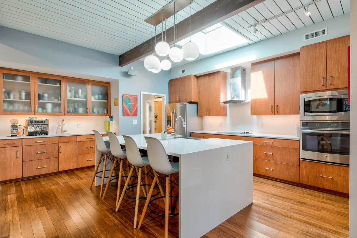 A kitchen features wood cabinets, a large island, and four bar stools.
