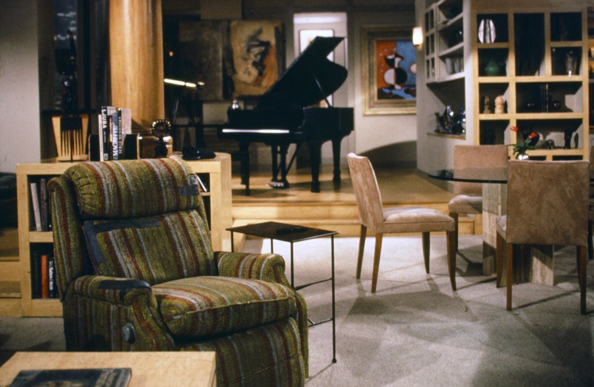 The living room from the TV show Frasier. There is a striped armchair in the foreground. In the distance is a grand piano and multiple works of art  on the walls.