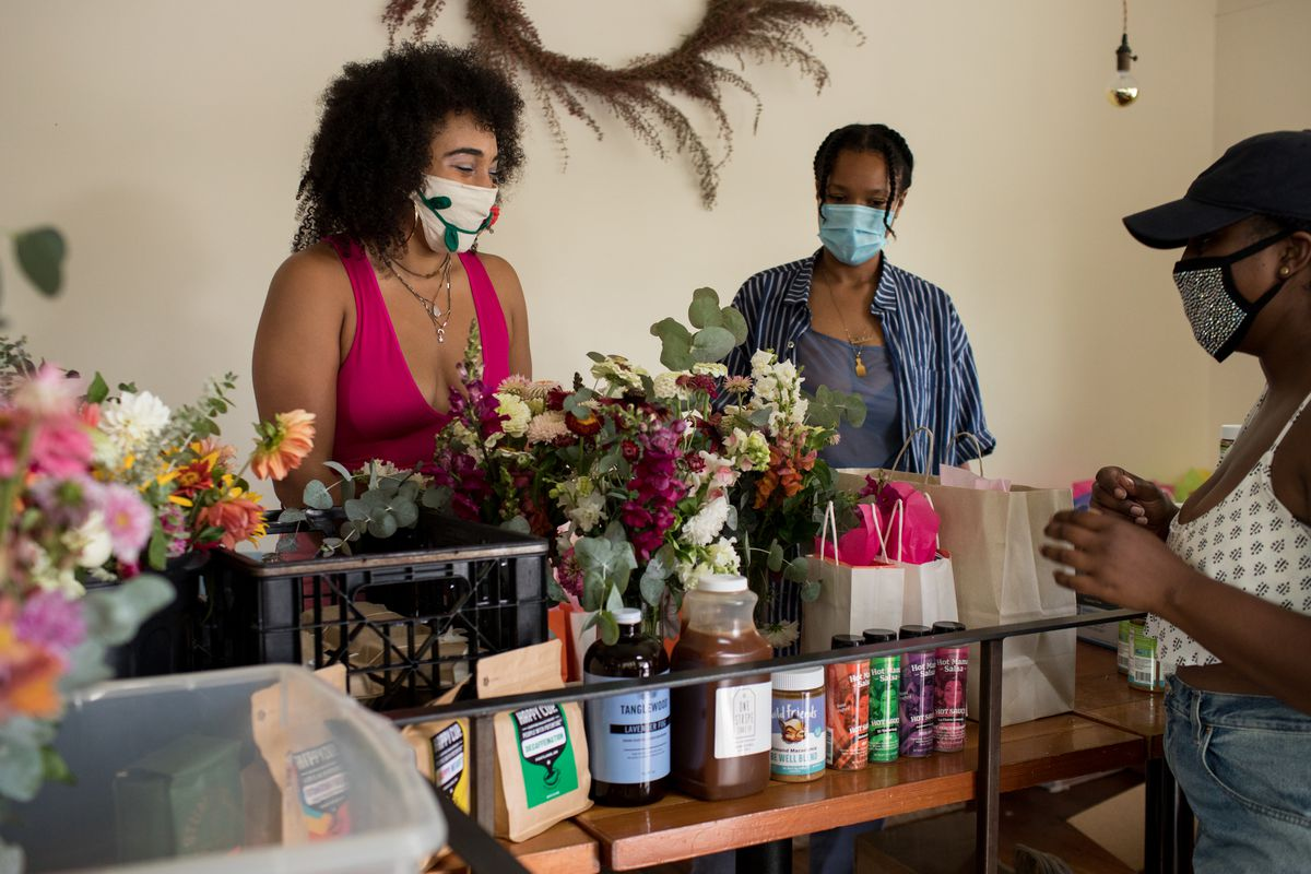 Two women standing behind a counter with one woman facing them on the other side. All are wearing face masks.