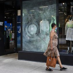 A woman walks past Nike at 669 N. Michigan Ave. on the Magnificent Mile after looting broke out overnight in the Loop and surrounding neighborhoods, Monday morning, Aug. 10, 2020.