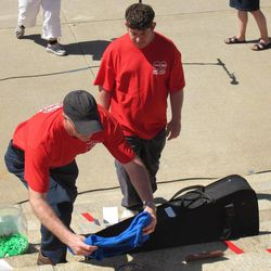 Jerry Michaud, left, president and chief executive officer of Developmental Services of Northwest Kansas, places a T-shirt for a display of personal items on the south steps of the Statehouse during a rally against Gov. Sam Brownback's plan to overhaul the state's Medicaid program. Watching to his right is Chad Ostmeyer, of Oakley.