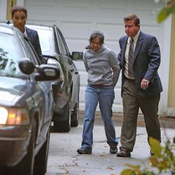 Annie Dookhan, center, is escorted to a cruiser outside her home in Franklin, Mass. Friday, Sept. 28, 2012. Dookhan is accused of faking drug results, forging signatures and mixing samples a state police lab. State police say Dookhan tested more than 60,000 drug samples involving 34,000 defendants during her nine years at the lab. Defense lawyers and prosecutors are scrambling to figure out how to deal with the fallout.
