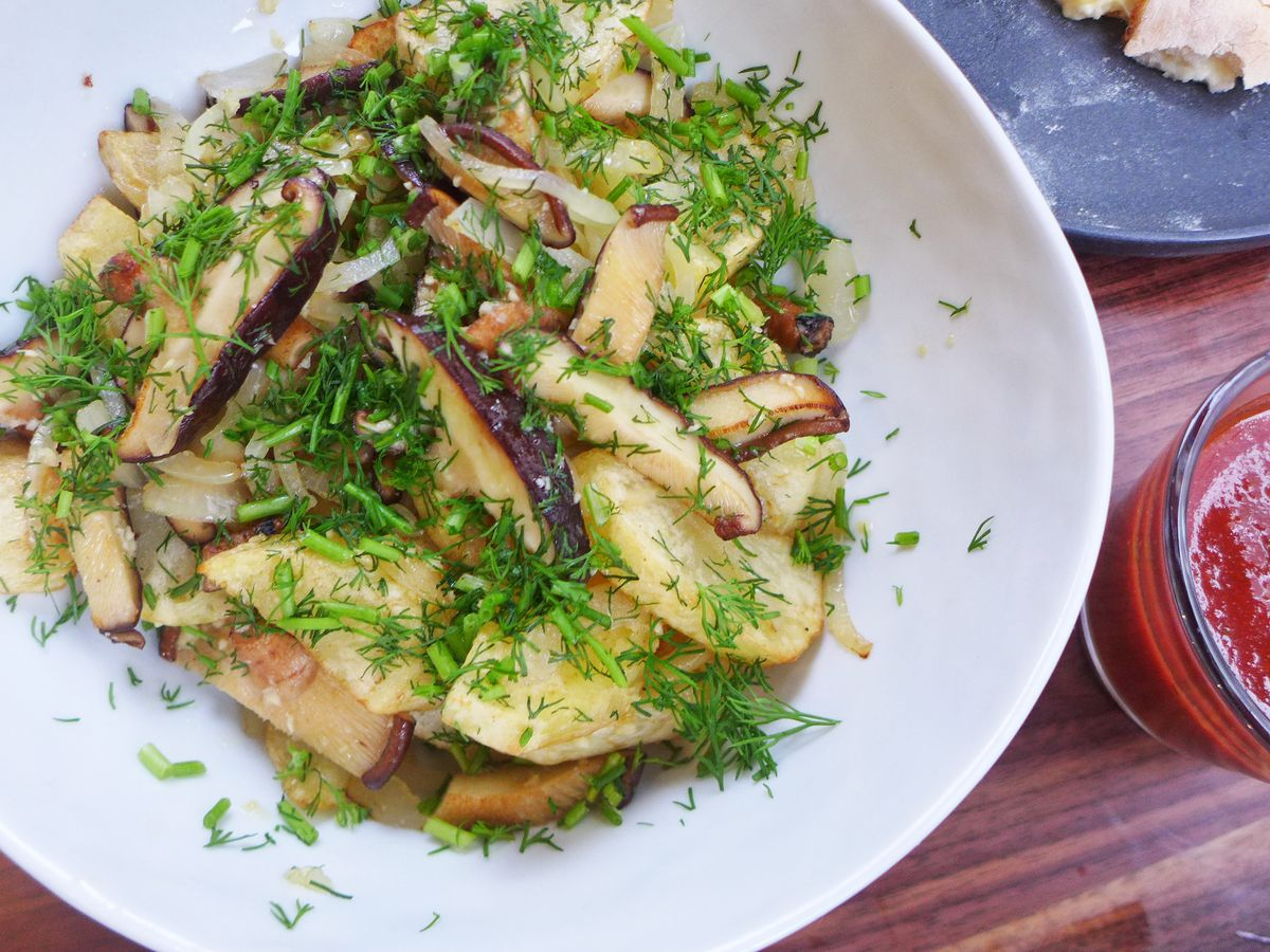 A white bowl of sliced potatoes and mushrooms partly hidden under green herbs.