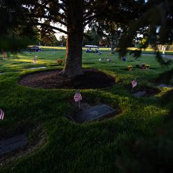 Flags are placed at graves at Larkin Sunset Gardens Cemetery in Sandy on Thursday, May 27, 2021. More than 200 youth volunteers from around the Salt Lake Valley honored military veterans for Memorial Day by placing 3,000 American flags on the graves of service members. In addition, they swept and polished headstones and helped beautify cemetery grounds.