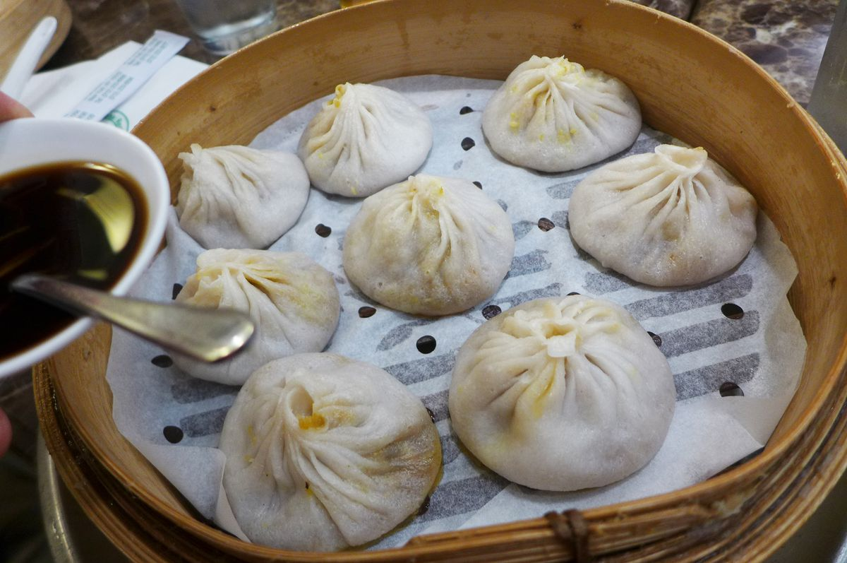 Eight puckered dumplings in a round steamer with parchment underneath.