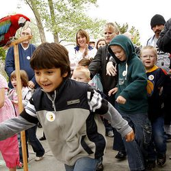 Children dash past Hogle Zoo's macaw after it cut the ribbon Saturday on the Conservation Carousel, which features animals in danger of becoming extinct.