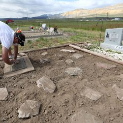 Curtis Larsen cleans the gravesite of his father at the Bingham City Cemetery in Copperton on Thursday, May 25, 2017. The Jordan School Board has deeded the pioneer cemetery to Copperton Township after 44 years as owner and caretaker.