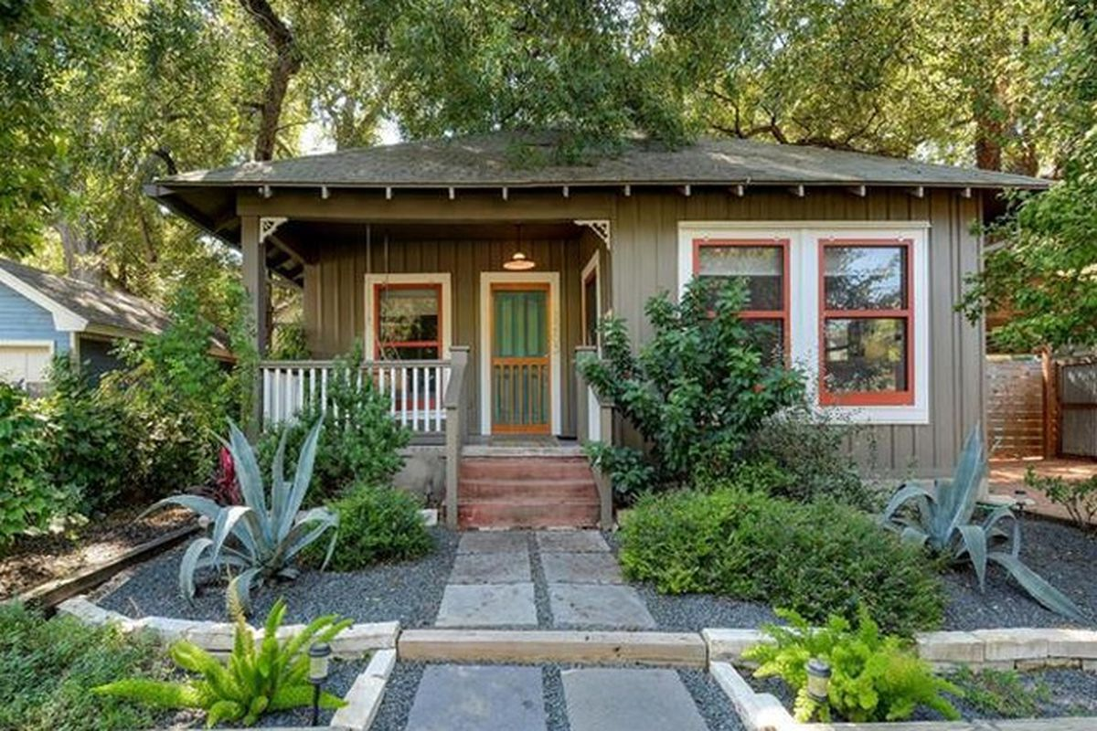 1940 wood frame square home with porch on one side, light brown, with white and orange window trim, big shrubs and yucca in front