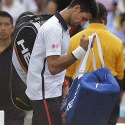 Serbia's Novak Djokovic walks off the court after the semifinal match against Spain's David Ferrer was postponed because of approaching inclement weather at the 2012 US Open tennis tournament,  Saturday, Sept. 8, 2012, in New York.