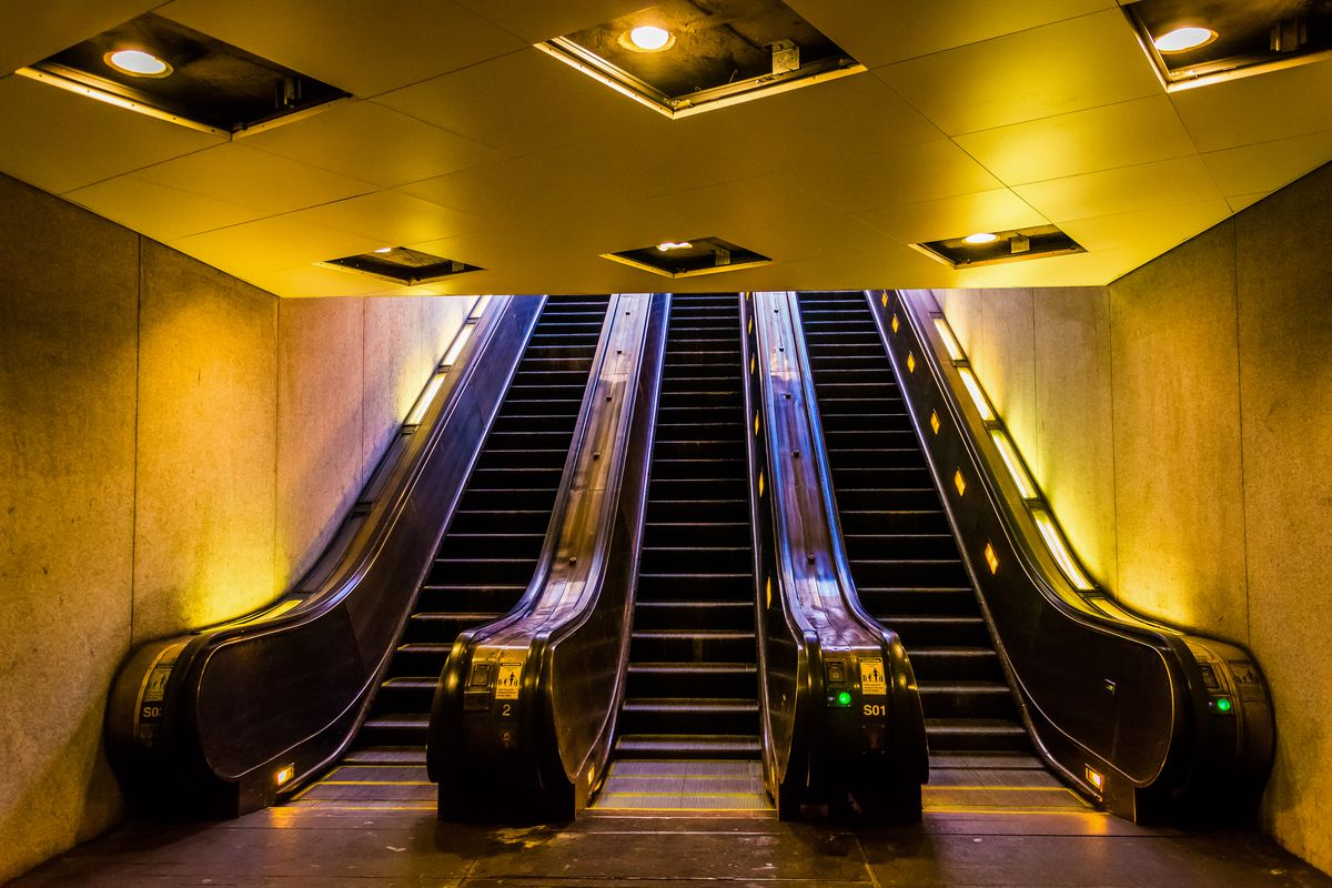 A set of three escalators in a subway seen from their base.